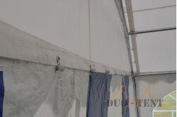 voorkant van partytent 6x12 met 6 meter breed oproldeur pvc zeil